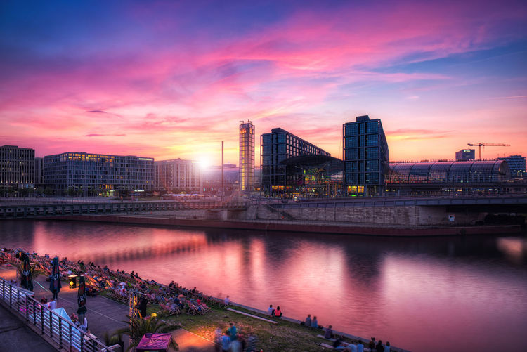 River By Buildings Against Cloudy Sky During Sunset