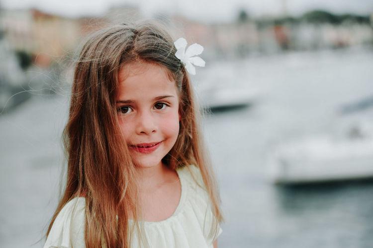 Portrait of smiling girl standing against river