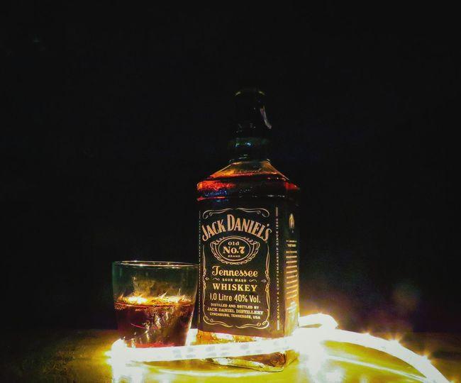 Close-up of illuminated bottle on table at night