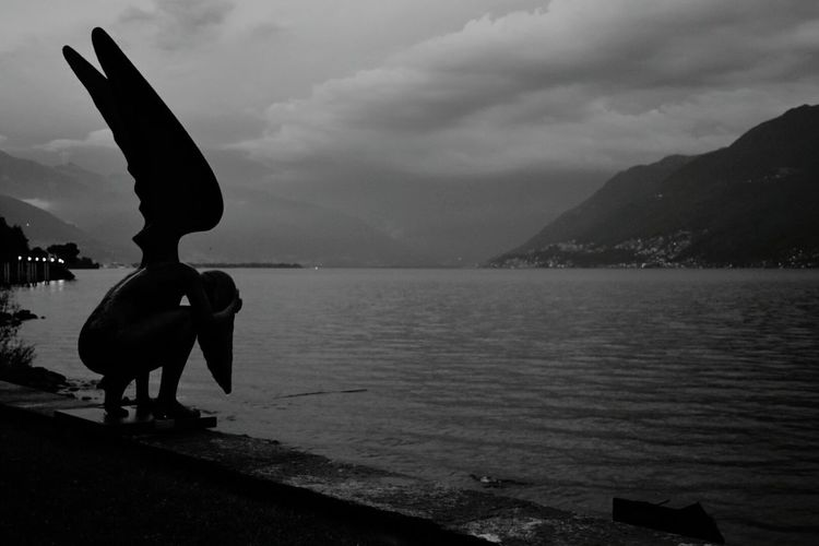 Statue at Lago Maggiore, Bressagio, Switzerland Sculpture Water Statue Silhouette Outdoors No People Beauty In Nature Lago Maggiore Lago Maggiore, Italy Lago Maggiore Morning Scene Blackandwhite Lake View Lakescape Lakeshore Your Ticket To Europe Travel Destinations Waterfront_challenge Lost In The Landscape Connected By Travel Black And White Friday HUAWEI Photo Award: After Dark Capture Tomorrow