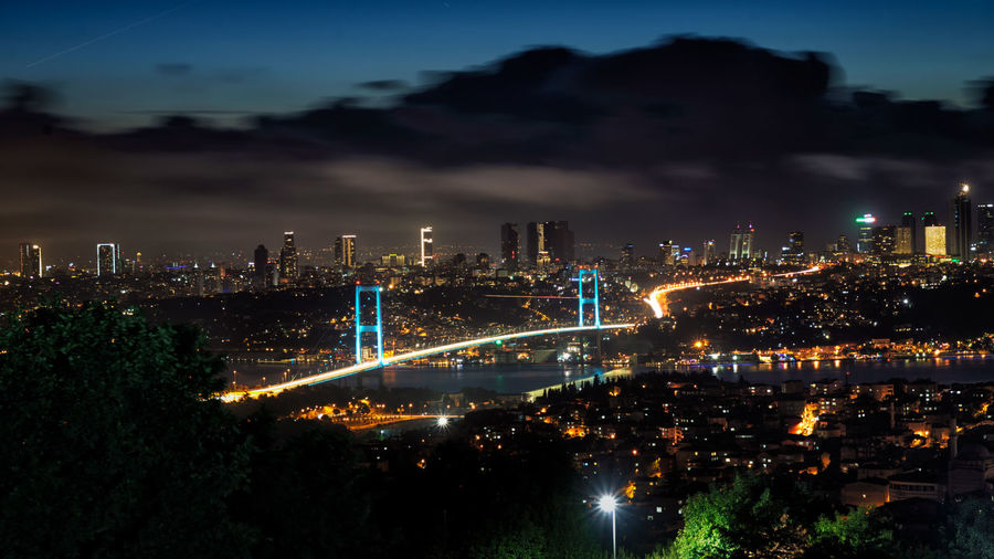 Illuminated bosphorus bridge in city against cloudy sky at night
