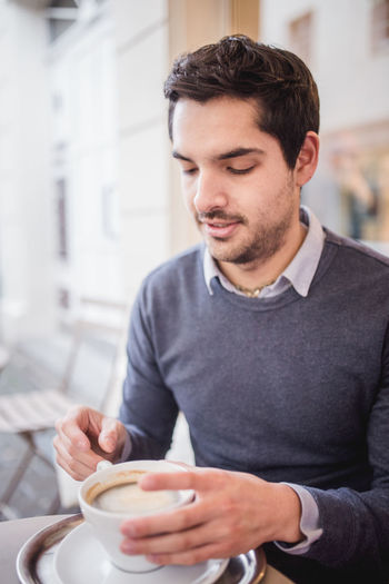 Young man is having a cup of hot coffee Business Coffee Going Out Relaxing Cafe Close-up Coffee - Drink Coffee Cup Drink Focus On Foreground Food Food And Drink Freshness One Person Refreshment Spare Time Young Adult Young Man