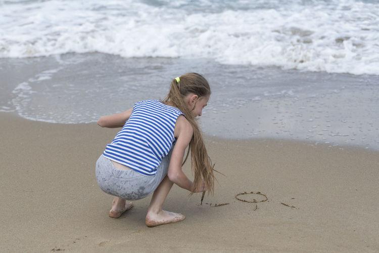 Full length of playful girl on shore at beach