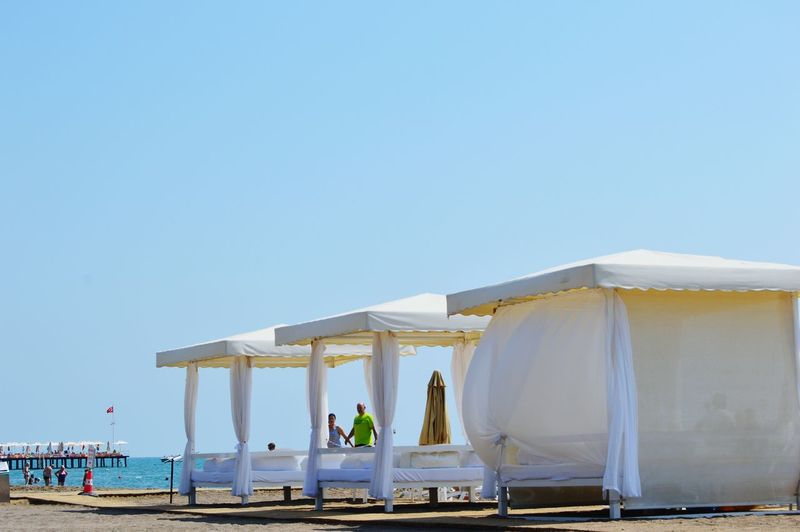 Four poster bed on beach against sky