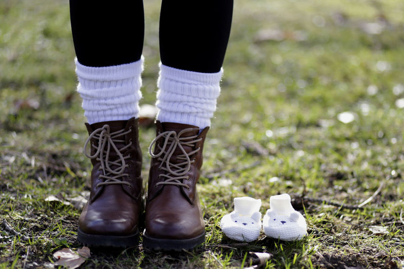 Low Section Of Woman Standing By Baby Boots On Field