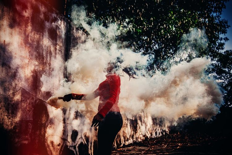 Woman holding distress flare against trees
