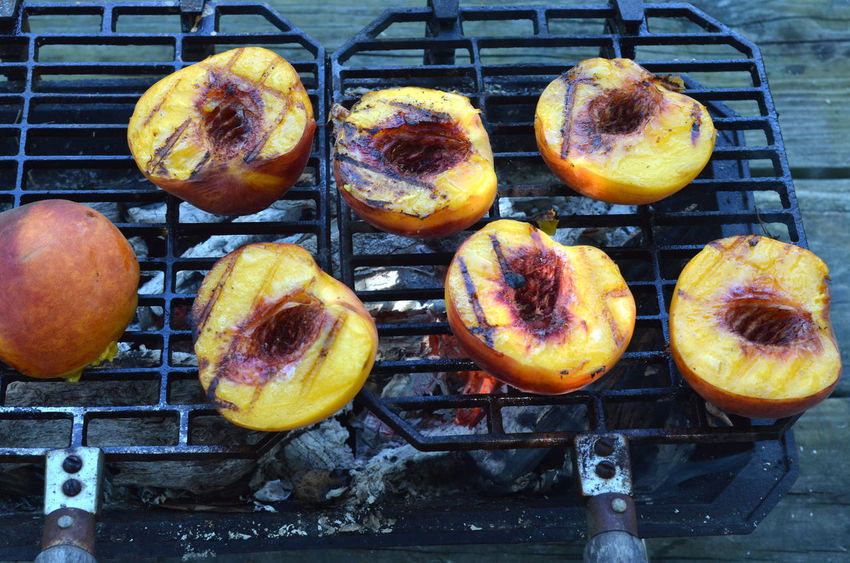Peach halves grilling on top of a small tabletop Hibachi grill on picnic table outdoors Abundance Barbecue Close-up Day Dessert Food Food And Drink Fresh Freshness Grill Grilled Peaches Grilling Group Of Objects Healthy Eating Hibachi Grill In A Row Indulgence Metal No People Peach Peach Halves Peaches Ready-to-eat Temptation