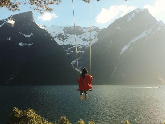 Woman swinging over calm lake against mountain range
