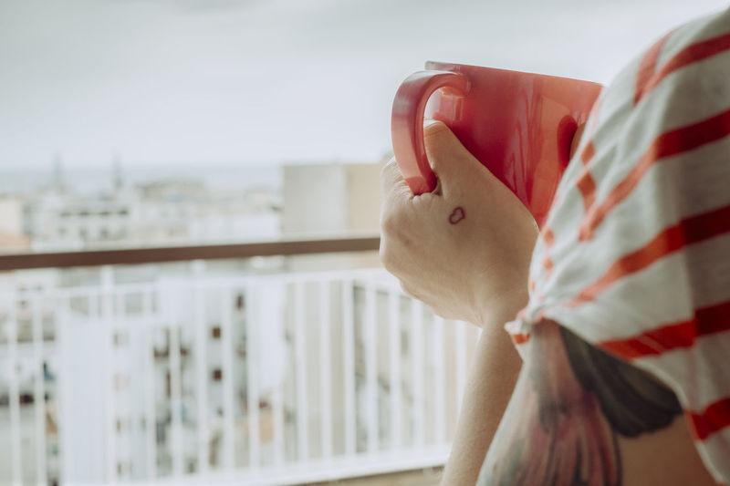 Close-up of woman holding red mug on balcony