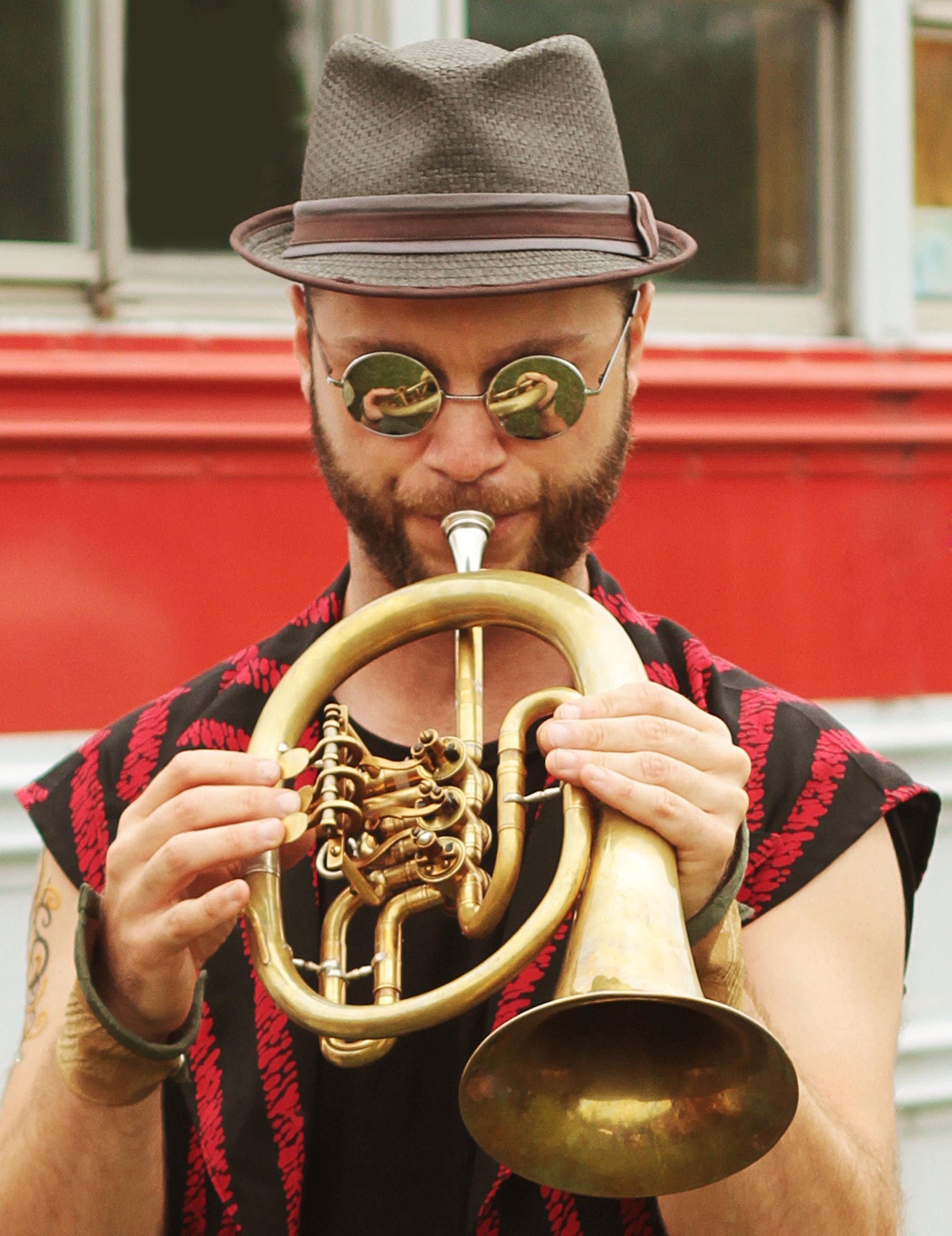 music, musical instrument, one person, hat, holding, front view, portrait, real people, leisure activity, clothing, lifestyles, artist, arts culture and entertainment, men, musician, brass instrument, brass, playing, males, trumpet, skill, mature men