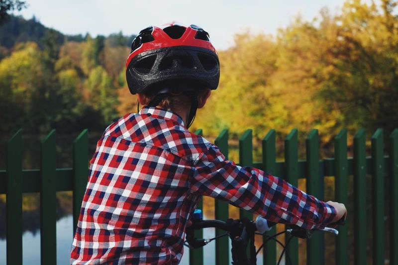 Rear view of boy wearing helmet with bicycle standing by fence against lake at park
