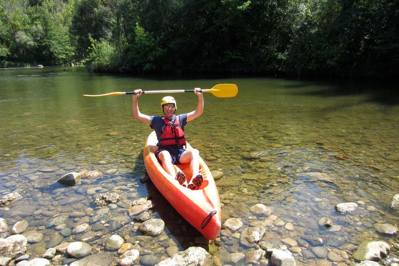 Excited man holding oar while sitting on kayak at riverbank