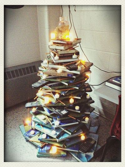 A Christmas Tree made out of Textbooks , Tea Lights , calculators and pencils at School
