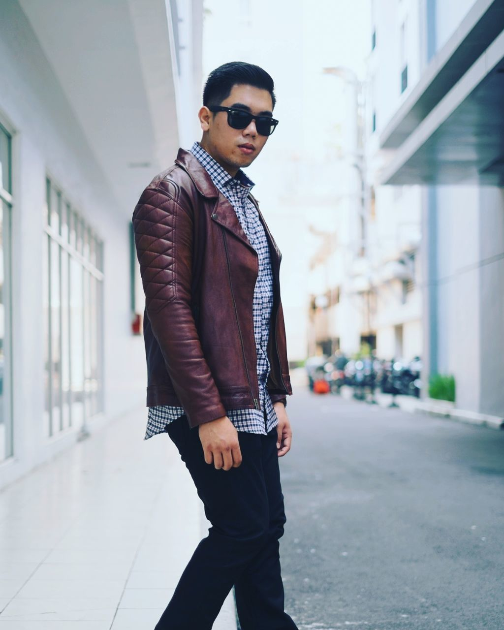 sunglasses, one person, young adult, young men, standing, fashion, focus on foreground, real people, hands in pockets, front view, jacket, building exterior, outdoors, looking at camera, well-dressed, portrait, attitude, lifestyles, men, handsome, day, shirt and tie, built structure, architecture, city, people