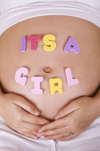 Close-Up Of Its A Girl Text On Pregnant Woman Abdomen
