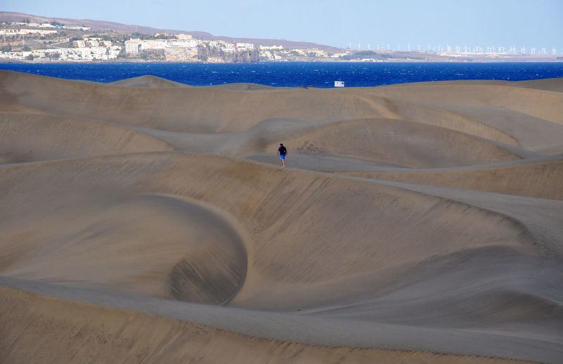 Man walking on sand dune