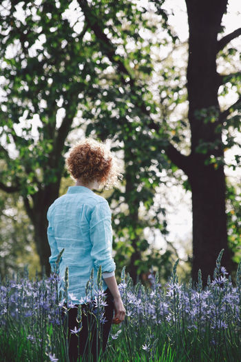Beauty In Nature Blonde Casual Clothing Curly Hair Day Flower Focus On Foreground Fragility Girl Green Color Growth Landscape Leisure Activity Lifestyles Nature Outdoors Park Plant Sky Spring Tranquil Scene Tranquility Tree Tree Trunk Breathing Space