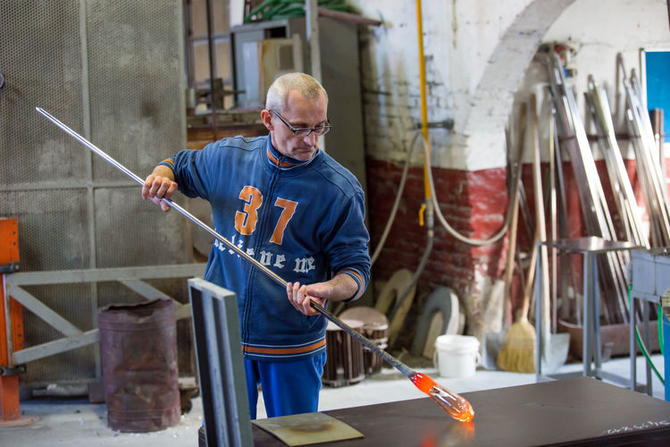 Adult Day Glass Factory Holding Indoors  Industry Manual Worker Manufacturing Occupation Mature Adult Mature Men Men Metal Industry Muranoglass Occupation Occupational Safety And Health One Person People Protective Workwear Real People Skill  Standing Welder Work Tool Working Workshop