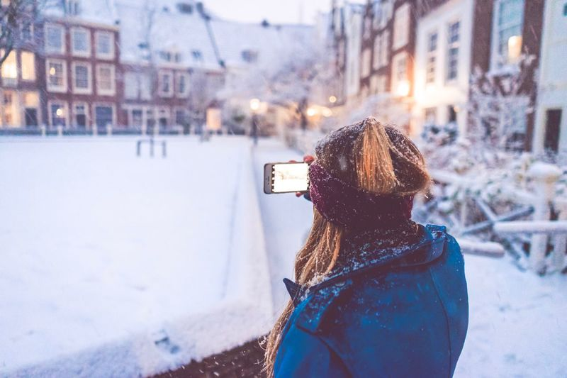 Amsterdam City Vibe Blue Jacket Red Headband IPhone Begijnhof Amsterdam Winter Cold Temperature Snow Building Exterior Real People Architecture Built Structure Photographing Warm Clothing Focus On Foreground Rear View Snowing