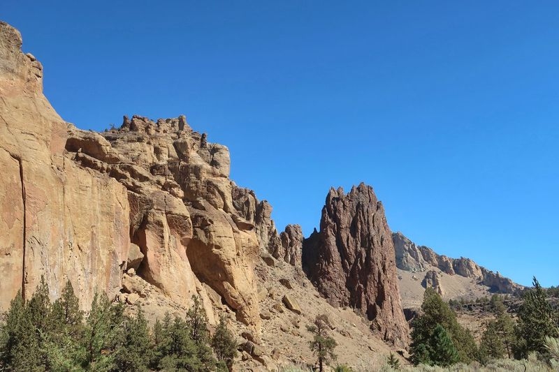 Low angle landscape of jagged vertical rock formations in Smith Rock State Park in Oregon Oregon Rock Formations Tourist Attraction  Travel Destinations Blue Sky Smith Rock State Park Sky Nature Blue Rock Clear Sky Low Angle View Tranquility Day Land Solid Tranquil Scene Sunlight No People Tree Copy Space Beauty In Nature Plant Scenics - Nature Rock Formation Rock - Object