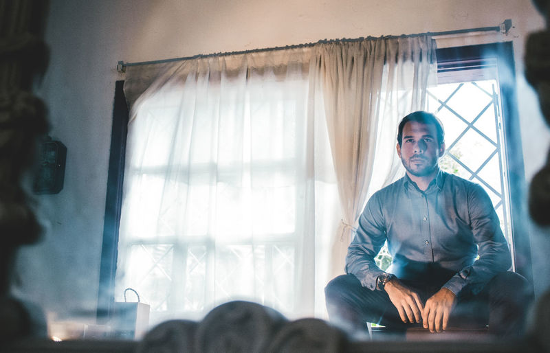 Serious man sitting on window sill reflecting in mirror