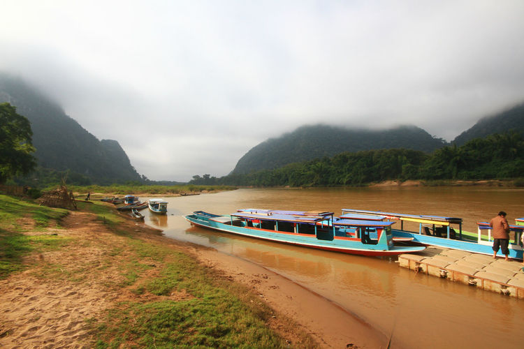 Row of boats in the river at country village in Muangngoi,Luangprabang,Laos. Riverside Beauty In Nature Boat Cloud - Sky Countryside Day Laos Laungprabang Long Tail Boat Mode Of Transportation Moored Mountain Mountain Range Nature Nautical Vessel No People Outdoors Passenger Craft River Scenics - Nature Sky Tranquil Scene Tranquility Transportation Water