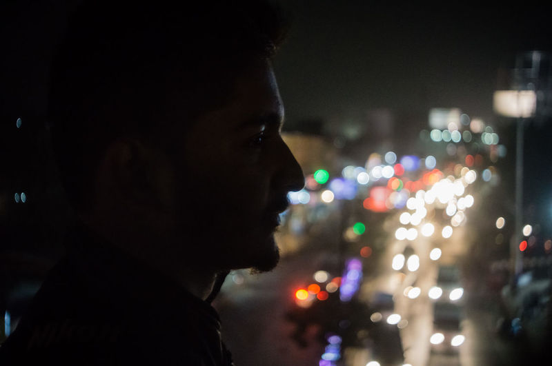 Close-up of man in illuminated city