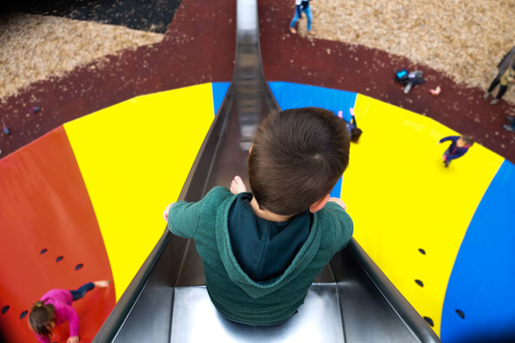 High angle view of boy on slide at playground