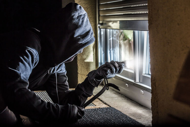 a burglar with a crowbar lights with a flashlight in a window Burglary Protection Crowbar Adult At Night Break Burglar Burglary Criminal Danger Dangerous Flashlight Hood Hood - Clothing Hooded Shirt Looking Men One Person Security System Steal Thief Window