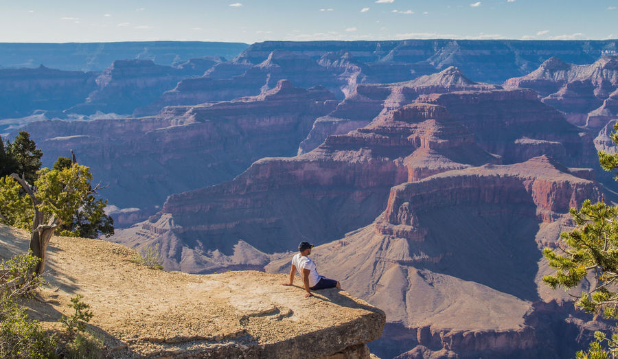High angle view of man sitting on cliff against canyon