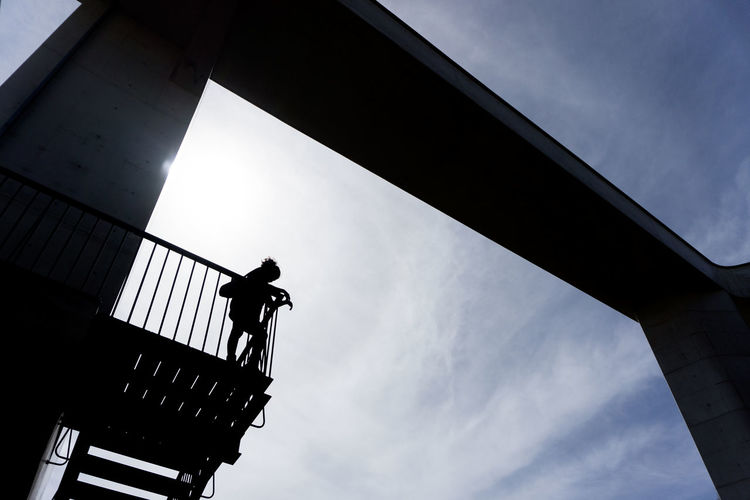 Low angle view of silhouette man standing on bridge against sky