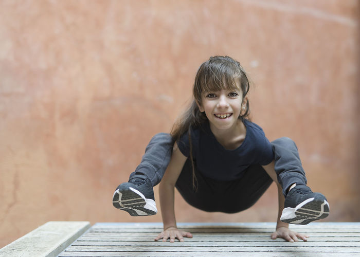 Portrait Of Smiling Girl Balancing On Hands Against Wall