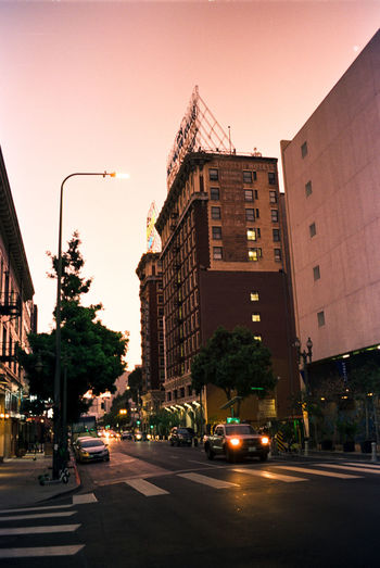View of city street and buildings at sunset