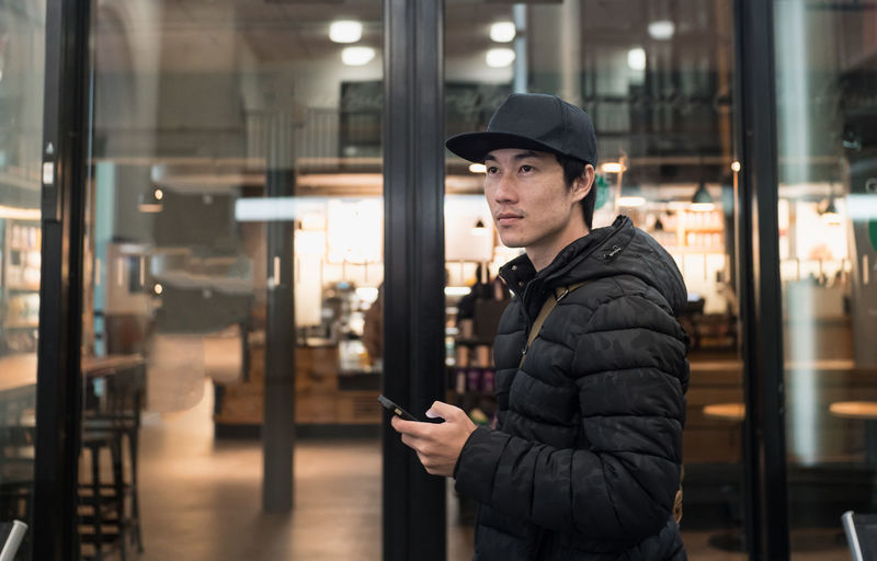Young man using mobile phone in illuminated building