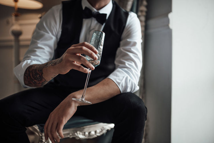 Midsection of man holding champagne flute