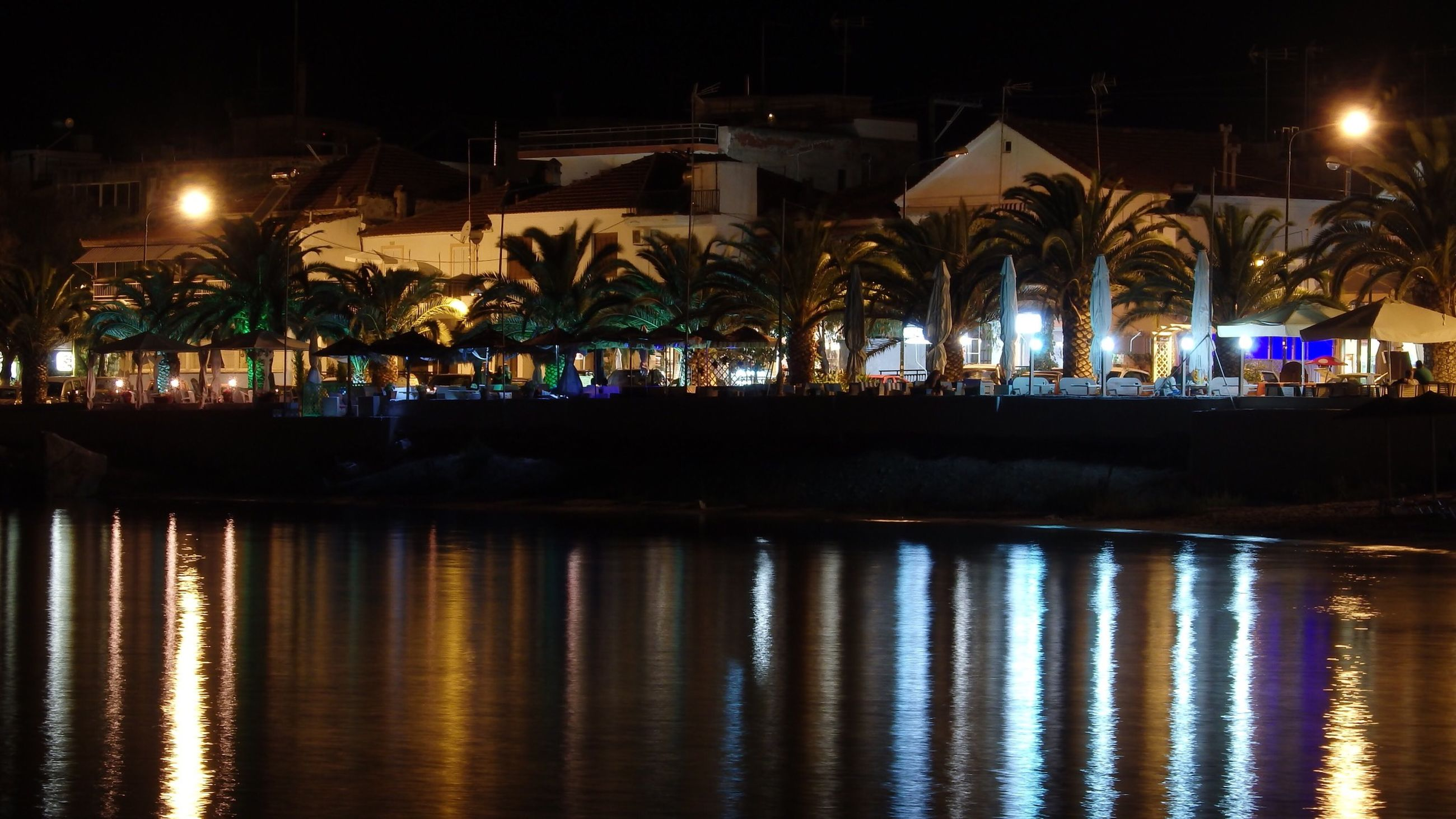 night, illuminated, water, reflection, built structure, architecture, waterfront, building exterior, river, street light, bridge - man made structure, lighting equipment, connection, outdoors, sky, no people, canal, pier, in a row, dark