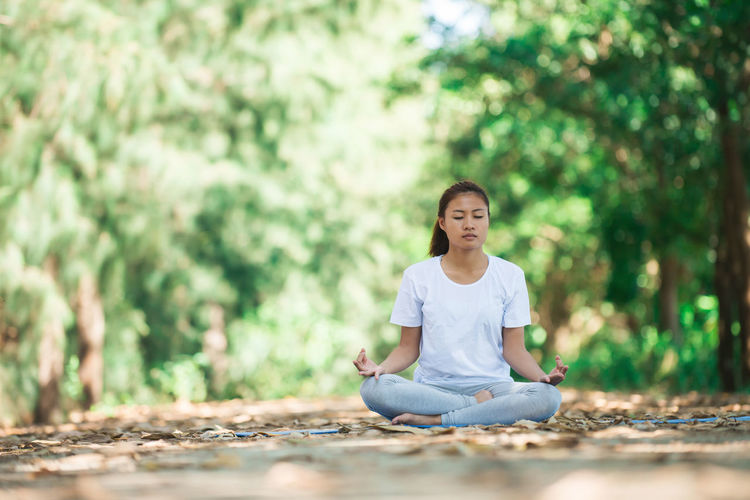 Young woman practicing yoga in lotus position at park