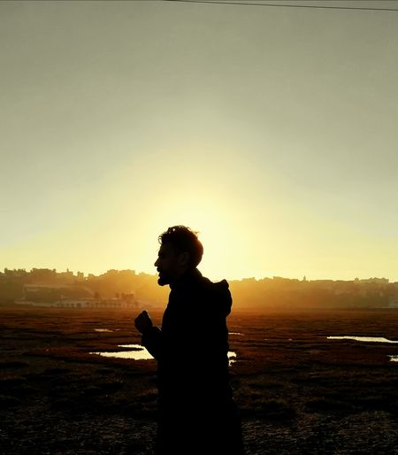 Side view of silhouette man standing on landscape against sky during sunset