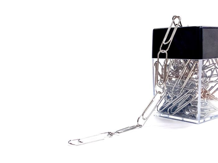A chain paper clips from its box made from transparent body with clips inside and black cover on white background. Abstract Chain Stationary Copy Space Indoors  Studio Shot Close-up White Background Still Life No People Business Paper Creativity Cut Out