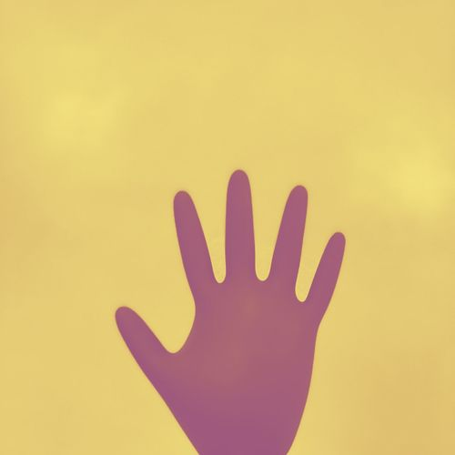 Close-up of human hand against yellow background