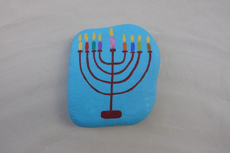 Symbol of jewish holiday Hanukkah with a painted stylized design of a Menorah, candlestick with nine candles over a stone Hanukkah Hanukkah Menorah Hanukkah Candles Jewish Hebrew Happy Hanukkah Stone Rock - Object Stone Design Design Symbol Creativity Art And Craft Art Work Artistic