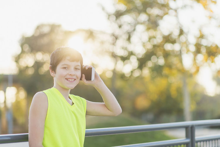 Portrait of a teenager smiling using his smartphone on a basketball court Casual Clothing Childhood Communication Day Focus On Foreground Front View Happiness Holding Leisure Activity Lifestyles Looking At Camera Mobile Phone One Person Outdoors Photographing Photography Themes Portable Information Device Portrait Real People Smiling Standing Technology Tree Waist Up Wireless Technology