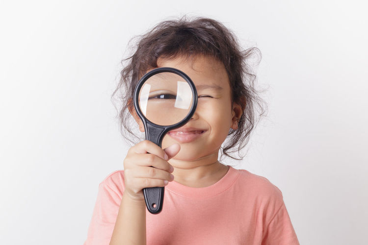 Portrait of girl looking through magnifying glass against white background