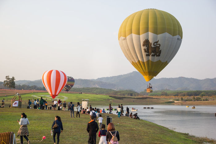 CHIANGRAI, THAILAND - FEBRUARY 15, 2017 : Hot air Balloons ready to rise into the sky in the sunset at SINGHA PARK CHIANGRAI BALLOON FIESTA 2017, Chiangrai province, Thailand Adult Air Vehicle Ballooning Festival Crowd Day Flying Grass Hot Air Balloon Landscape Large Group Of People Leisure Activity Outdoors People Sky