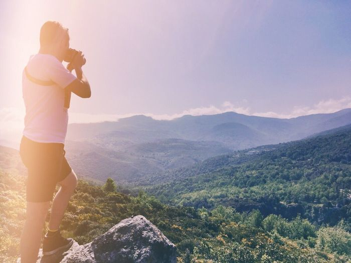 Man Photographing Mountains Against Sky On Sunny Day