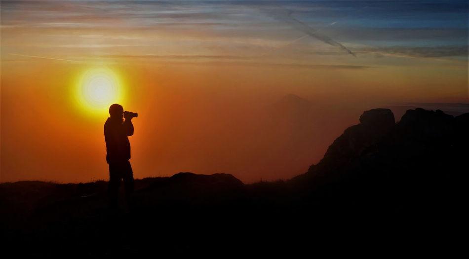 Silhouette man standing on mountain against orange sky