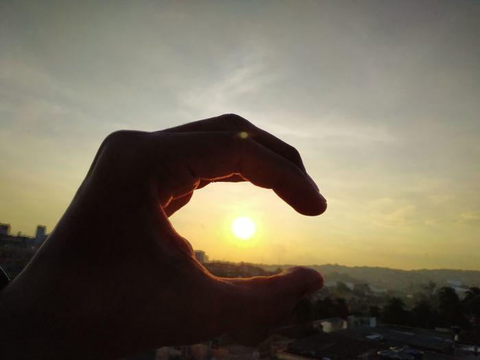 Human hand holding sun during sunset