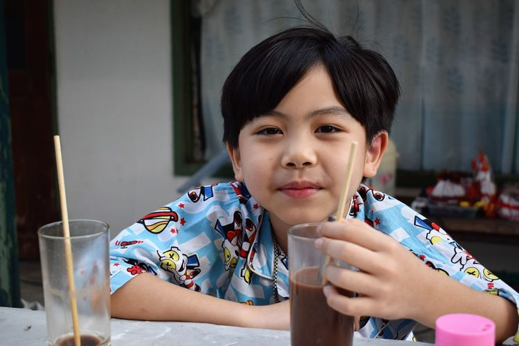 Portrait of boy having chocolate drink at home