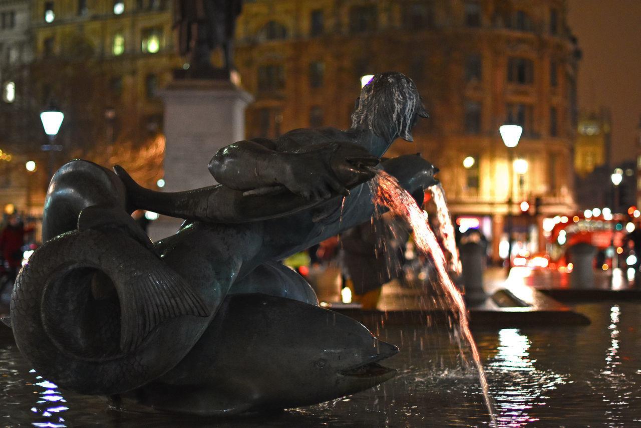 Fountain In Illuminated City At Night