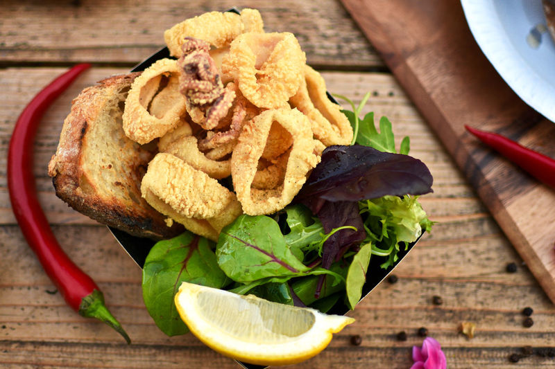 Close-up of bread and fried calamari in bowl on table